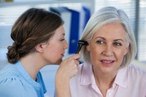 doctor examining patient's ear with os
